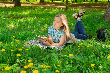 Beautiful young woman lying, thinking and writing in her diary on the grass with flowers. Front view.