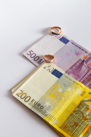 Two engagement rings and euro banknotes isolated on white background Фото со стока