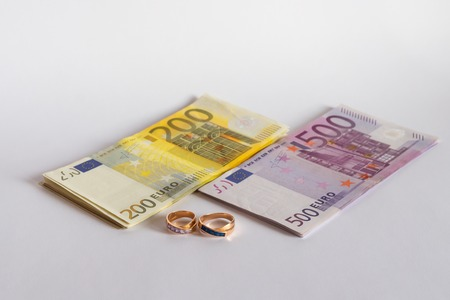 Two engagement rings and euro banknotes isolated on white background