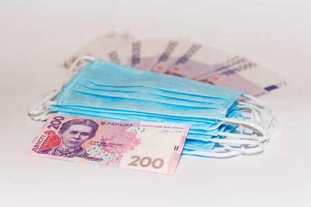 Protective medical mask and Ukrainian hryvnia. Expensive medicine concept.