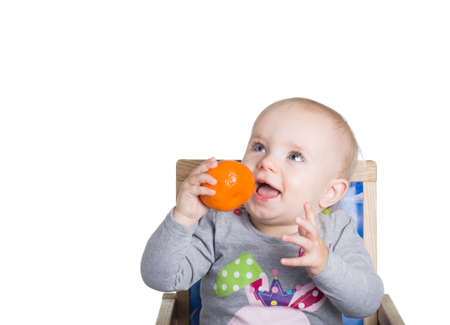 child with an orange looks up Stock Photo - 16909128