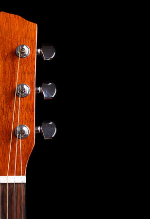 Top of guitar neck over black background