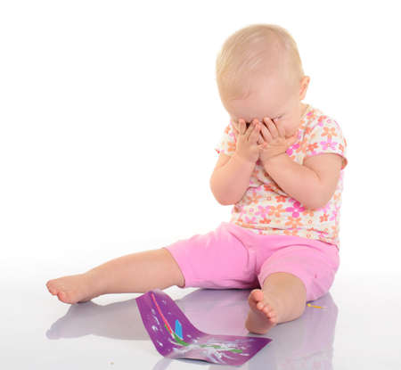 nurseling: Baby playing with a picture on white background
