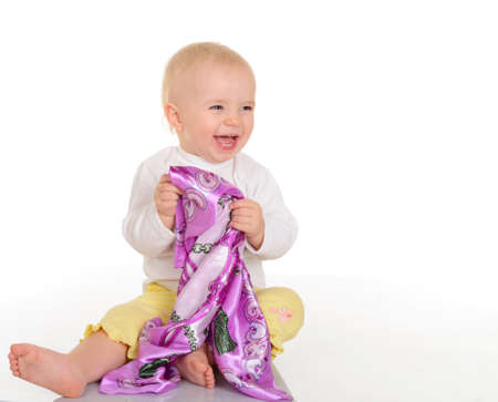 baby girl playing with kerchief on white background