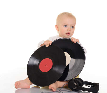 baby playing with old vinyl record and headphones on white background