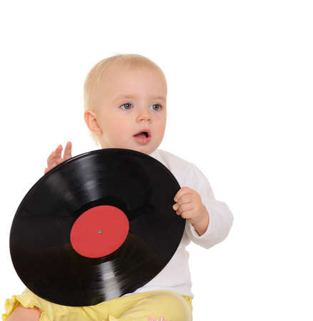 cute baby playing with old vinyl record on white background