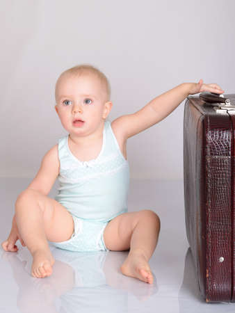 cute baby girl playing with suitcase on grey background Stock Photo - 18124751
