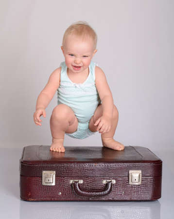 cute baby girl playing with suitcase on grey background Stock Photo - 18124667