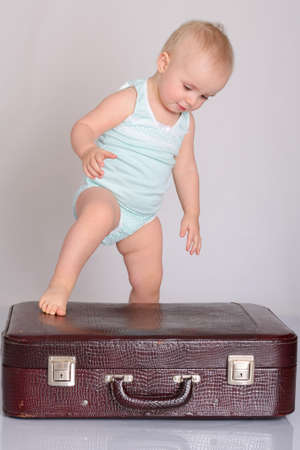 cute baby girl playing with suitcase on grey background Stock Photo - 18124754