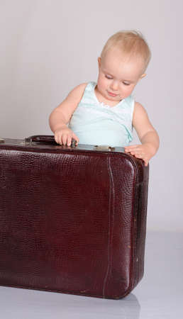 cute baby girl playing with suitcase on grey background