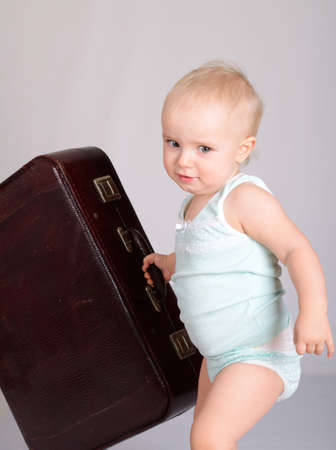 cute baby girl playing with suitcase on grey background Stock Photo - 18124678