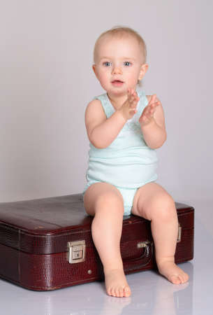 cute baby girl playing with suitcase on grey background Stock Photo - 18124743