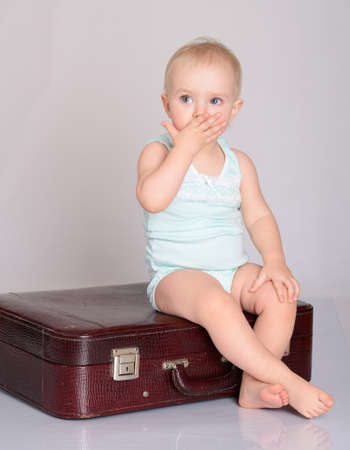 cute baby girl playing with suitcase on grey background Stock Photo - 18124748