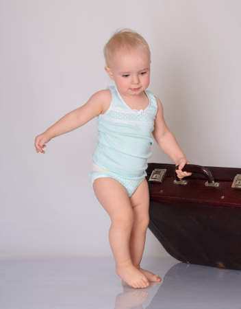 cute baby girl playing with suitcase on grey background Stock Photo - 18124739