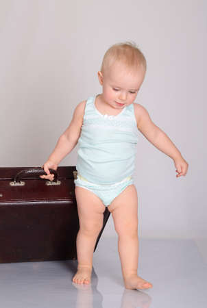 cute baby girl playing with suitcase on grey background Stock Photo - 18124741