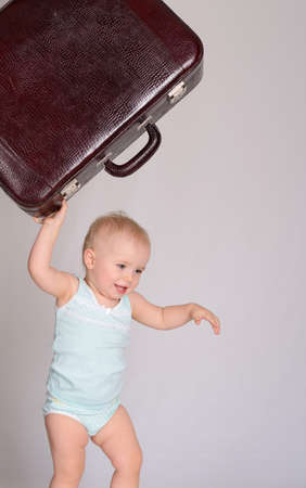 cute baby girl playing with suitcase on grey background photo