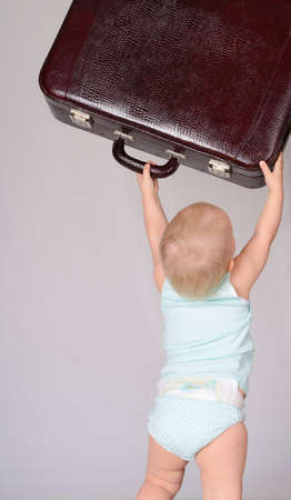 cute baby girl playing with suitcase on grey background Stock Photo - 18124668