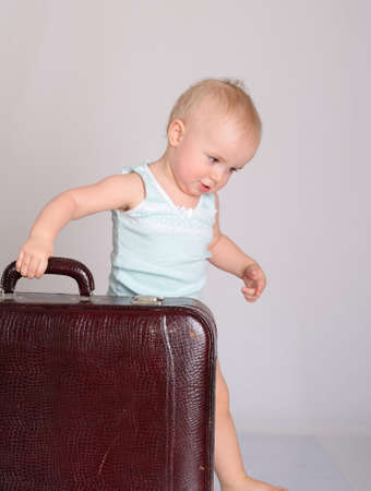 cute baby girl playing with suitcase on grey background Stock Photo - 18124752
