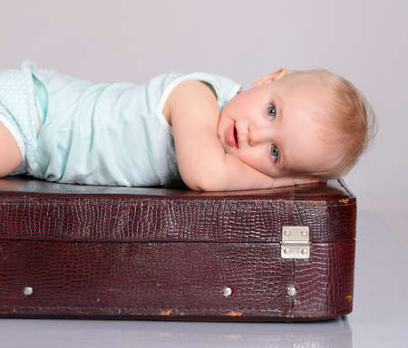 cute baby girl playing with suitcase on grey background Stock Photo - 18124742