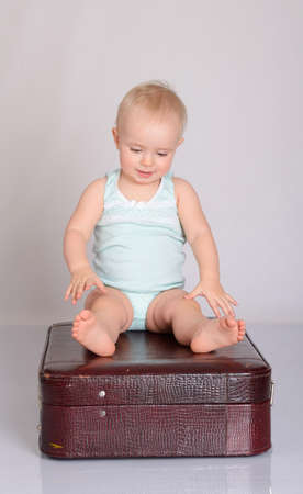 cute baby girl playing with suitcase on grey background Stock Photo - 18124756