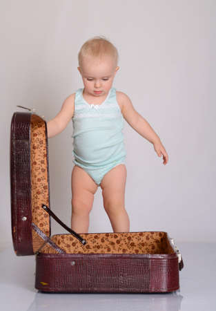 cute baby girl playing with suitcase on grey background Stock Photo - 18124746