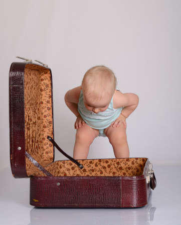 cute baby girl playing with suitcase on grey background Stock Photo - 18124753