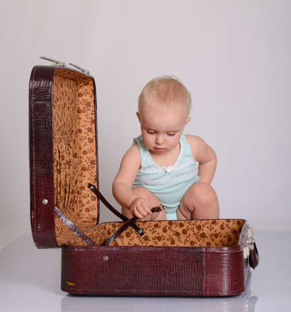 cute baby girl playing with suitcase on grey background Stock Photo - 18124757