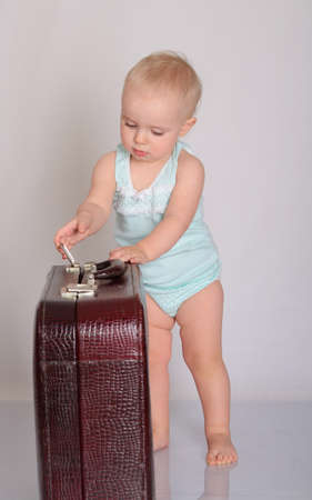 cute baby girl playing with suitcase on grey background Stock Photo - 18124749
