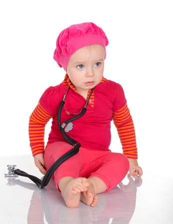 Qute baby girl with phonendoscope sitting on a white background Stock Photo