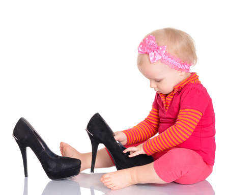 Cute little baby girl dressed in red trying on her mother's shoes on white background photo