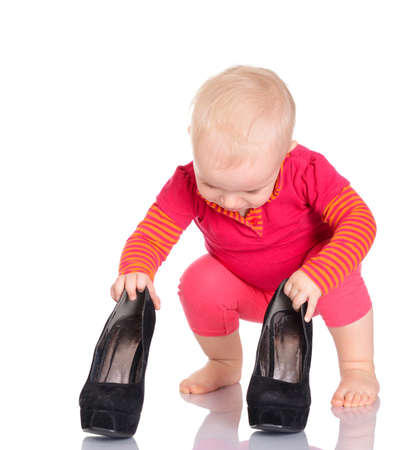 Cute little baby girl dressed in red trying on her mothers shoes on white background