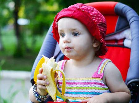 baby sitting in a pram eating banana Stock Photo
