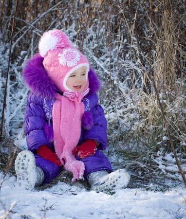 Portrait of happy little girl in snowy landscape photo