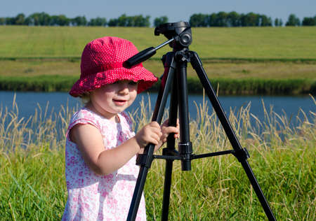 Little Photographer with Professional Tripod, River Background,  Outdoor Stock Photo