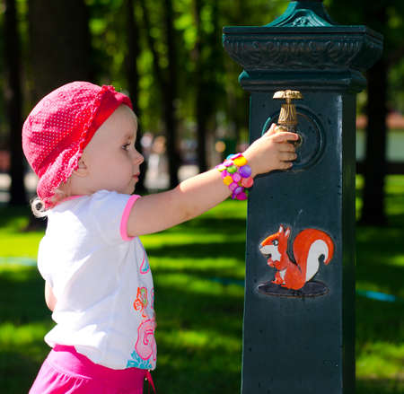 Smart Cute Girl near the Tap, Park,  Outdoor Stock Photo