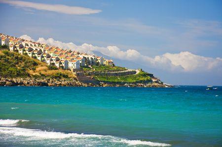 Beach view of hill with many houses, Kusadasi, Turkey photo