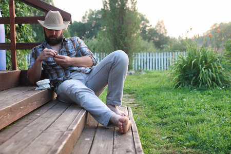 cowboy beard: man smoke pipe outdoor on village outdoor in summer Stock Photo