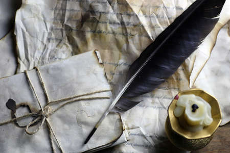old paper letter and black feather on wooden table