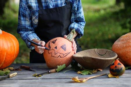 carve: person hands carve pumpkin for Halloween