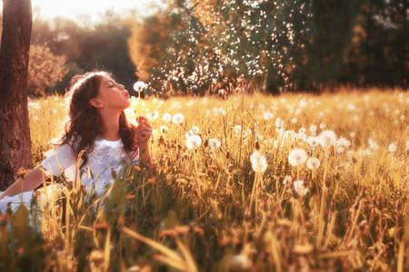 girl in white dress blow dandelion in outdoor Standard-Bild