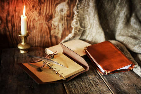 old retro styled composition of book candle and feather Stock Photo