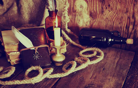 carabineer: old retro styled composition of book candle and feather Stock Photo