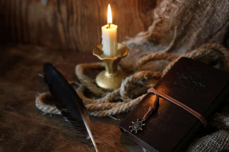inkstand: old retro styled composition of book candle and feather Stock Photo