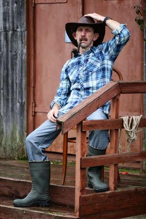 village man: cowboy old man smoke pipe on village outdoor