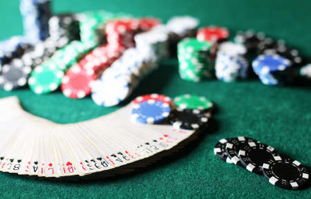 Poker chips and cards on the green cloth