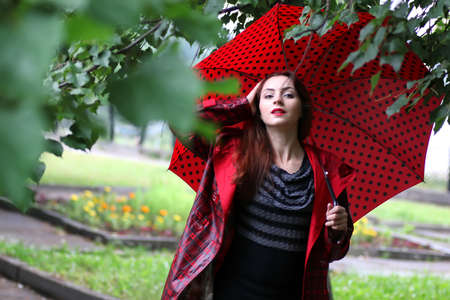 woman in a raincoat with an umbrella outdoor