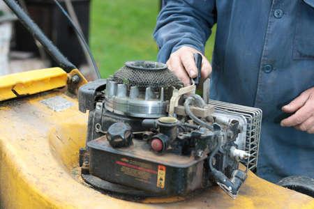 old man repairing lawn mower engine outdoor