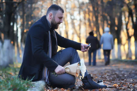 man in autumn park outdoor with bouquet flower date waiting