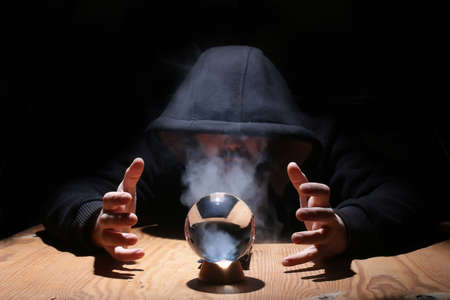 soothsayer: man in a black hood with cristal ball summon evil Stock Photo