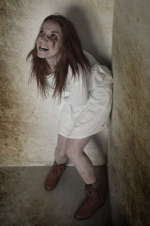 insane insanity: Portrait of a young red-haired girl on a background of gray plaster wall